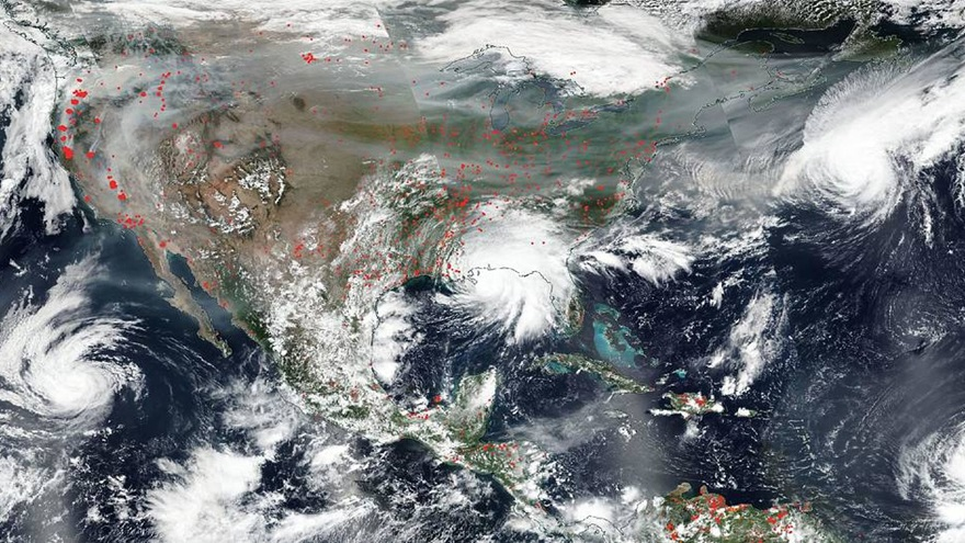 NASA's Aqua satellite captured this true-color image of the United States on Sep. 15, 2020, showing the fires in the West, the smoke from those fires drifting over the country, several hurricanes converging from different angles, and Hurricane Sally making landfall. Red points in the west note areas that are significantly higher in temperature than the areas around it and are indicative of fires. Image courtesy of NASA Worldview, Earth Observing System Data and Information System (EOSDIS).
