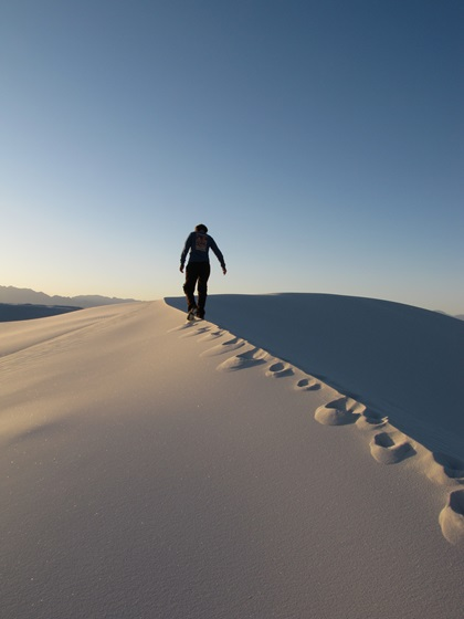 A hiker walks across the top of a dune at White Sands National Park. Photo courtesy of the National Park Service.