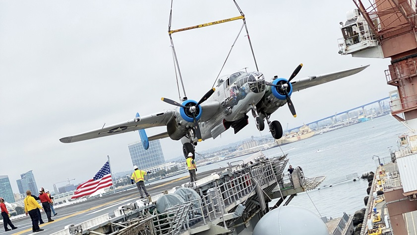 "The B-25 ""Old Glory"" is loaded onto an amphibious assault ship ""USS Essex"" by crane for transport to Hawaii to participate in an aerial parade commemorating the seventy-fifth anniversary of the end of World War II. Photo courtesy of the Prescott Foundation."