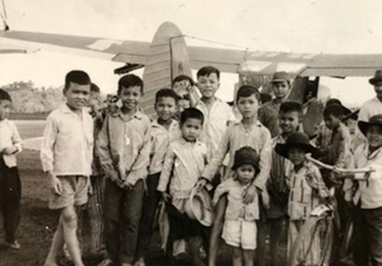 """Ron Allen gave rides to Southeast Asia youth during breaks from his missions in a Cessna O-1E Bird Dog airplane when he served in the Vietnam War. The photo of youth surrounding the single-engine liaison and observation aircraft was taken in 1966 at Bao Loc, Lam Dong Province, Republic of Vietnam. Allen said he """"would fold down the rear rudder pedals, remove the stick and strap them in, sometimes four at a time. It was great fun, and a nice break from being shot at."""" Photo courtesy of Ron Allen."""