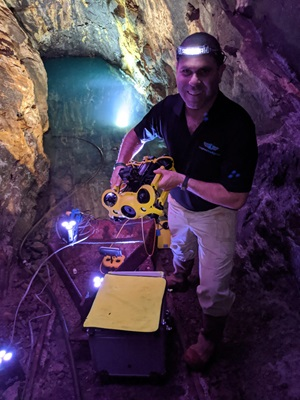 Nir Pe'er, CEO and founder of Inspired Intelligence, holds the M2 underwater drone after a scan was completed in one of the water-filled mine tunnels. Photo courtesy of Inspired Intelligence.