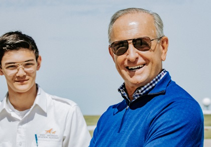 High school senior Aidan Nacke, shown with West Michigan Aviation Academy founder Dick DeVos, was the 100th student to earn a private pilot certificate. Photo courtesy of West Michigan Aviation Academy.