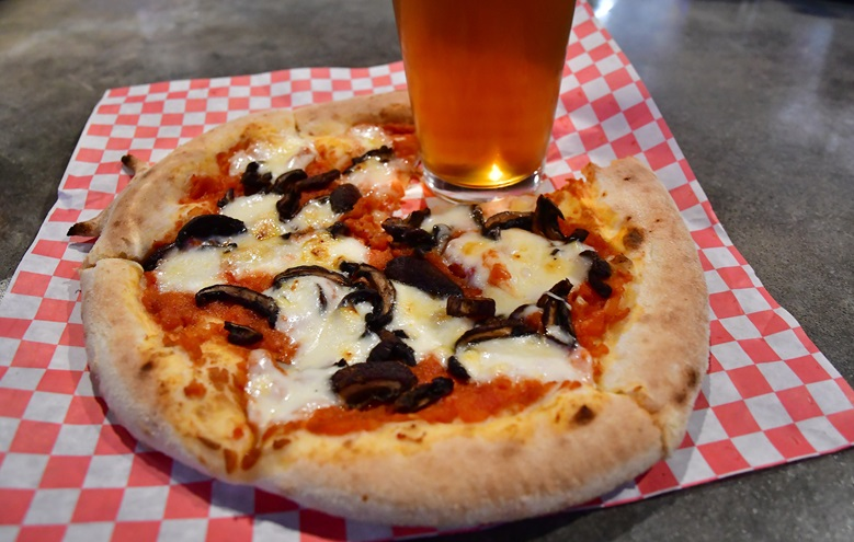 A fresh-baked pizza and a beer await a visitor to the Hunter-Gatherer Brewery inside the restored Curtiss-Wright Hangar at Jim Hamilton-L.B. Owens Airport near downtown Columbia, South Carolina. Photo by David Tulis.