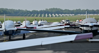 A variety of Mooney Aircraft airplanes are tied down on the ramp at Dane County Regional Airport-Truax Field in Madison, Wisconsin. Pilots joining the mass arrival to EAA AirVenture at Wittman Regional Airport must participate in at least one of several formation flying clinics presented across the United States and demonstrate proficiency. Photo by David Tulis.