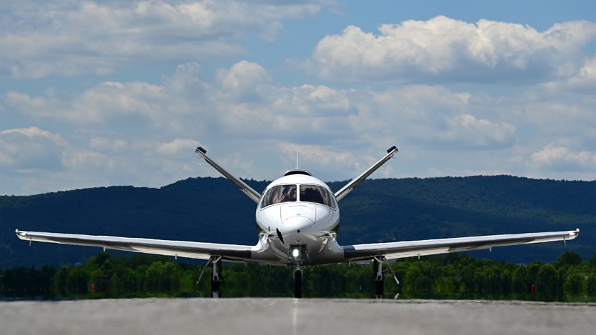 A Cirrus Vision Jet G2+ is framed by mountains near the Runway 12 threshold at Frederick Municipal Airport, June 23, 2021. Photo by David Tulis.