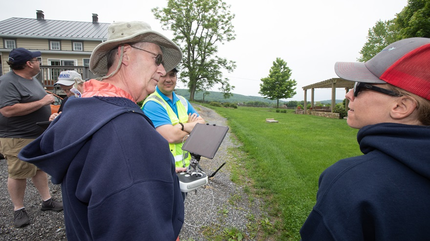 Engineer Michael Whitcomb, left, consults with his teammate, retired U.S. Marine Corps Capt. Shelby Goudy, during a mapping exercise led by DARTdrones instructor Colin Romberger (background) during a class held during a 2019 AOPA Fly-In. Jim Moore photo.
