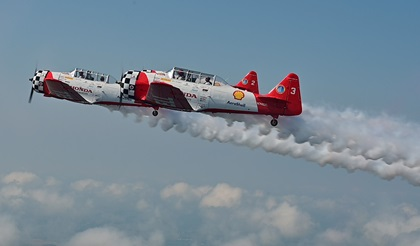 """""""Smoke on!"""" AeroShell Aerobatic Team pilots Steve Gustafson and Bryan Regan fly North American T-6 Texans in formation during EAA AirVenture in Oshkosh, Wisconsin. Photo by David Tulis."""