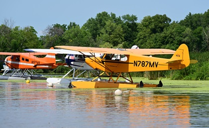 Seaplanes are moored in a cove at the EAA Seaplane Base on Lake Winnebago during EAA AirVenture in Oshkosh, Wisconsin. Photo by David Tulis.